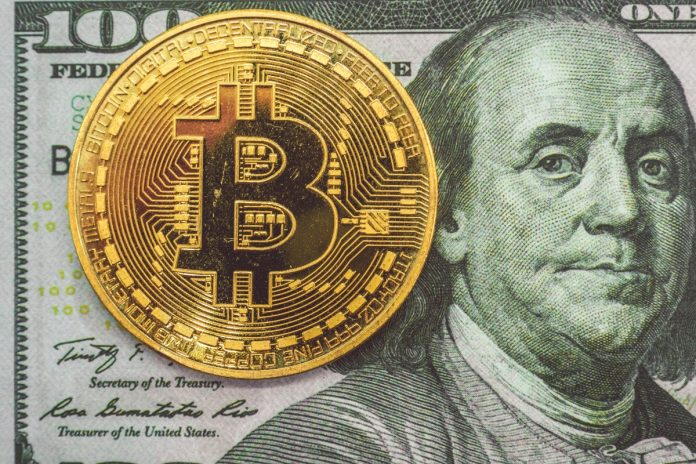 A bitcoin in front of a $100 bill. Depicting that crypto isn't money